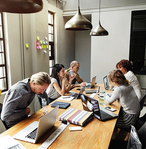 Ludzie pracują i rozmawiają przy laptopach